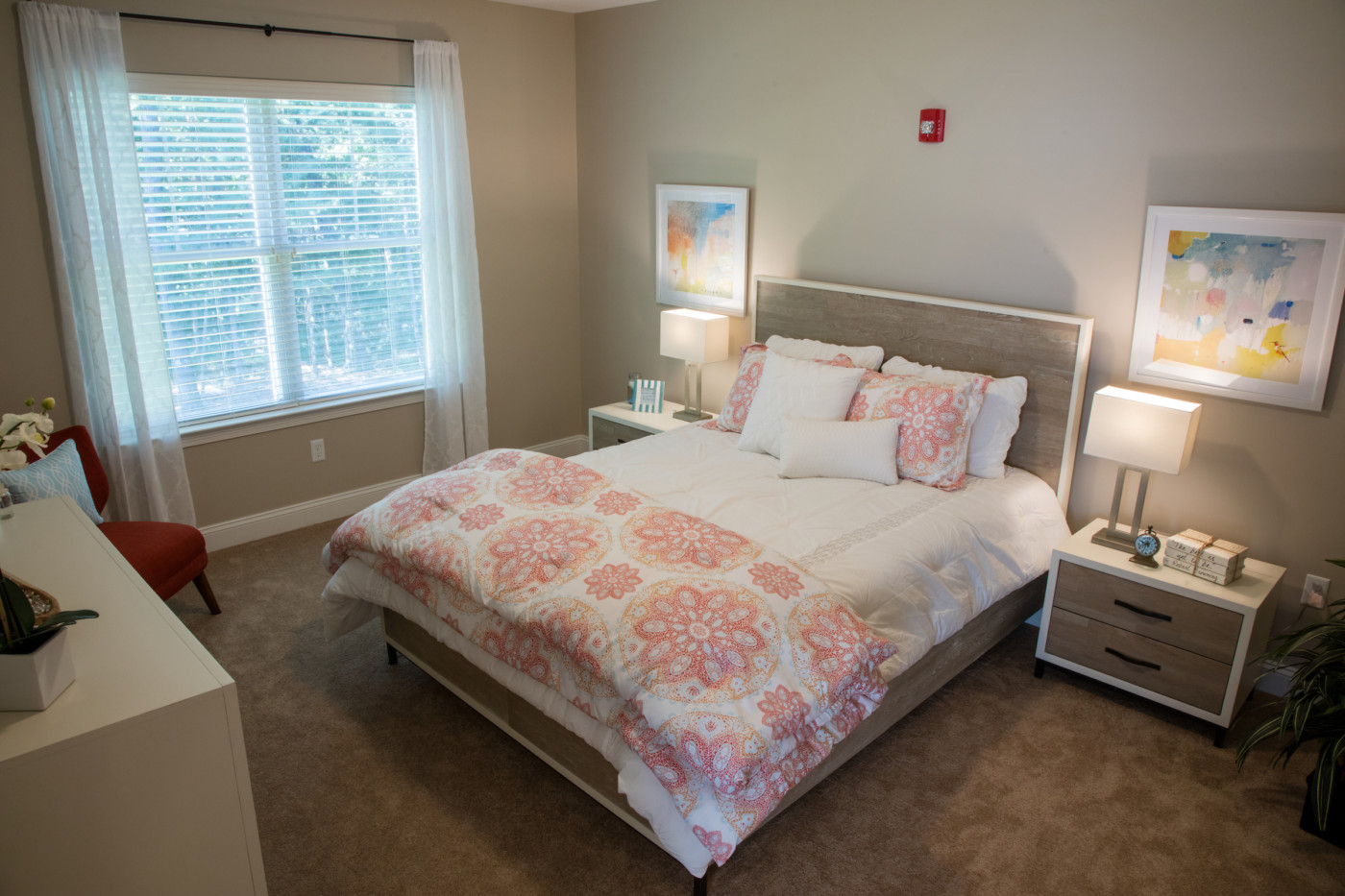 bedroom with coral bedding and light wood side tables