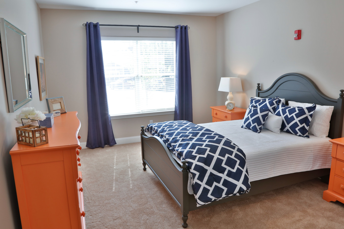 bedroom with orange side tables and dresser